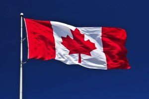 Flag of Canada waving in the wind on blue sky background